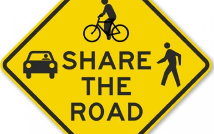 "A ""Share the Road"" traffic sign with car, pedestrian and bicyclist depicted"